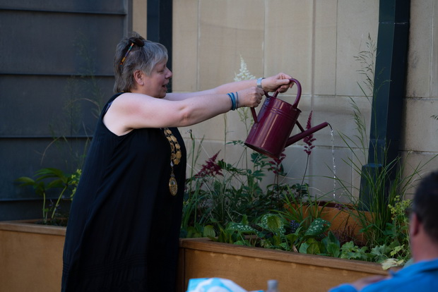 Hebden Royd Mayor Carol Stow 'opens' the scheme by watering a rain garden planter using its monitoring system